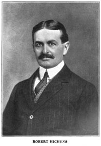 Middleaged man with moustache dressed in dark suit jacket, stiff-collared shirt and tie.