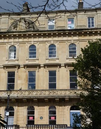 Grand 4-storey Italianate style terraced house, circa 1850, faced with pale Bath stone with an ornate carved stone balcony on the first floor.