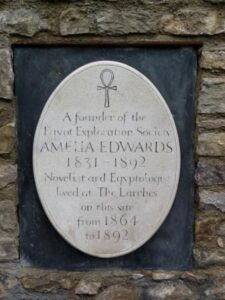"""Wall plaque with text """"A founder of the Egypt Exploration Society, Amelia Edwards 1831-1892, novelist and Egyptologist lived at The Larches on this site from 1864 to 1892""""."""