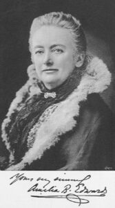 Head and shoulders of woman about 60, with an assured but warm face, wearing sheepskin lined jacket and neckscarf.