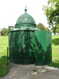 Ornate circular cast-iron hut about 3m diameter, with domed top, painted green.