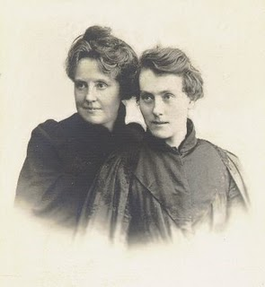 Two women, heads touching, Katharine about late 30s with rounded face, Emma early 20s and narrow face