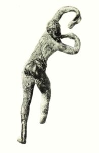 Rear view of bronze statue of naked young man, arms curled above head and posturing his buttocks