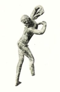 Side view of bronze statue of naked young man, arms curled above head and posturing his buttocks