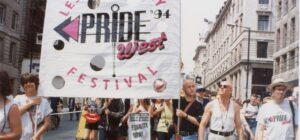 """Street parade with two men carrying a banner with wording """"Lesbian and gay Pride West '94 festival""""."""