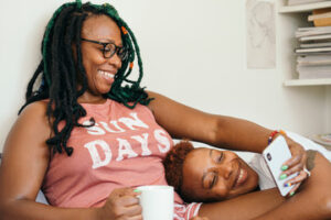 Two black women cuddling, one with her head in the other's lap.